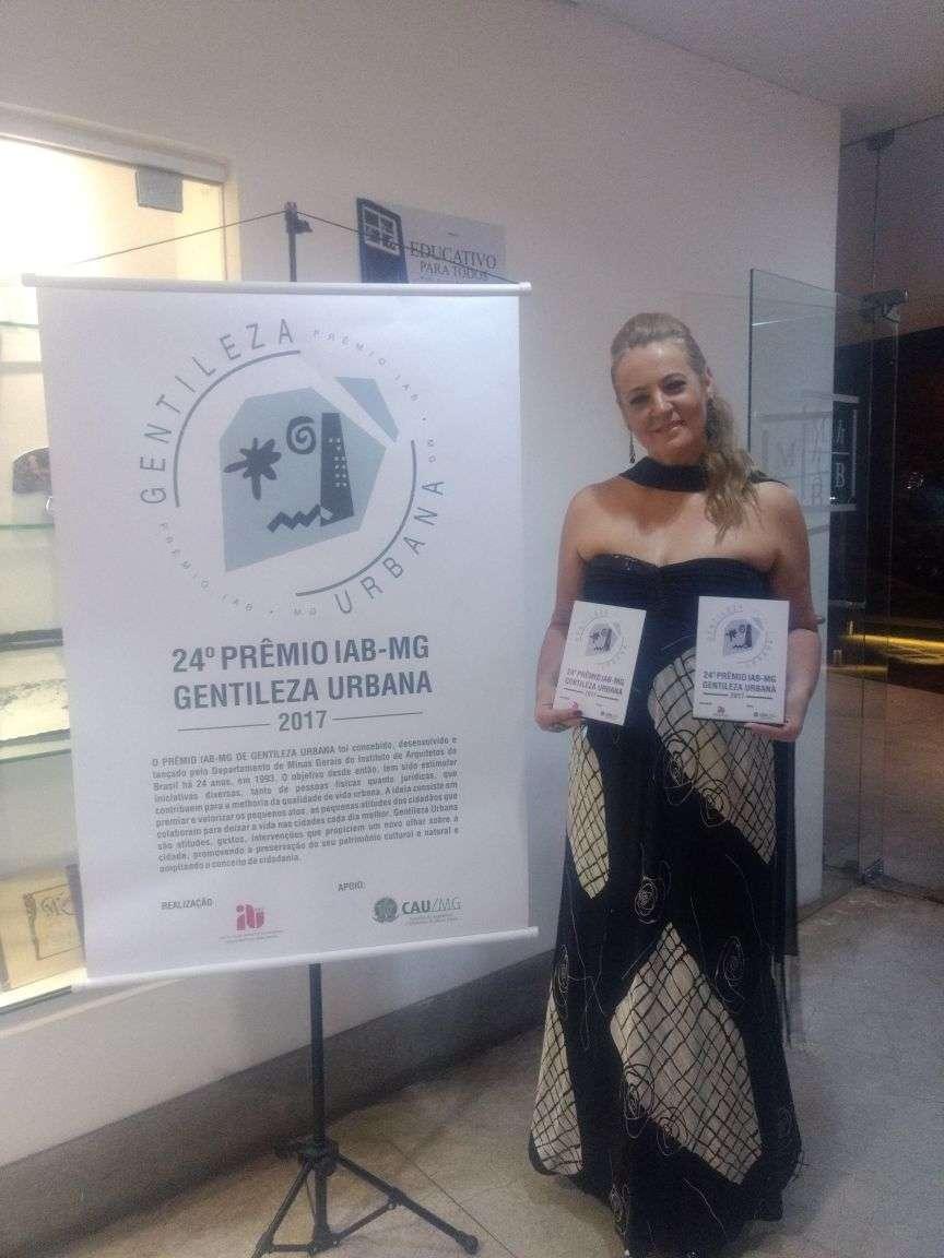 Gracielle Torres segurando seus dois prêmios por seus projetos de Gentileza Urbana