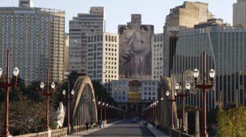 Foto do viaduto Santa Tereza, em Belo Horizonte. Uma arte em um prédio alto aparece ao fundo.